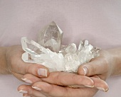 Hände halten Bergkristall
