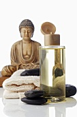 Massage oil and warm stones, Buddha figure in background