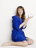 Woman in bathrobe holding jar of cream