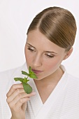 Woman smelling a sprig of fresh mint