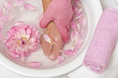 Woman washing her foot with pink peeling glove