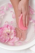 Woman washing her foot with pink sponge