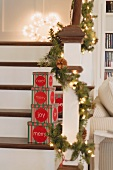 Boxes of Christmas decorations & fir garland on staircase