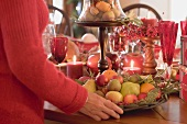 Woman placing bowl of fruit on table laid for Christmas