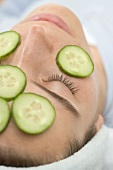 Woman with slices of fresh cucumber on her face