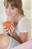 Woman holding glass of carrot juice