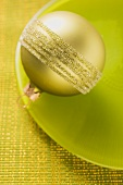 Gold Christmas tree bauble on green plate