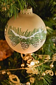 Painted bauble on artificial Christmas tree