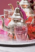 Silver teapot, glasses and windlights on tray