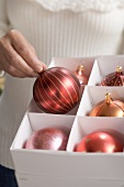 Woman taking red Christmas bauble out of box