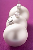 Three silver Christmas baubles