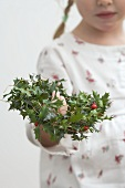 Small girl holding holly wreath