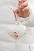 Child's hand holding Christmas tree ornament