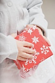 Small girl holding box with snowflake motifs