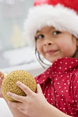 Small girl in Father Christmas hat holding Christmas bauble