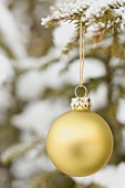 Christmas bauble on snow-covered fir branch out of doors