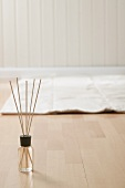 Incense sticks and mat on parquet floor