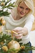 Frau hängt goldene Kugel auf Christbaum