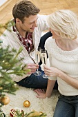 Couple clinking glasses of sparkling wine beside Xmas tree