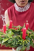 Woman blowing out candles on Advent wreath