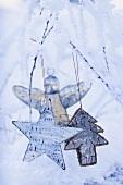 Sterne und silberner Engel auf verschneiten Zweigen