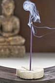 Incense stick in front of Buddha statue