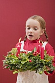 Small girl blowing out candles on Advent wreath