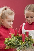 Two small girls blowing out candles on Advent wreath