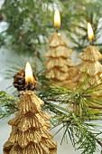 Goldfarbene Weihnachtskerzen zwischen Kiefernzweigen