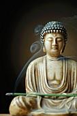 Buddhafigur mit Räucherstäbchen