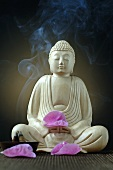 Buddha figure with incense sticks and flower petals