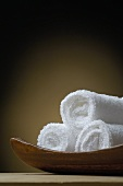 Rolled white towels in wooden dish