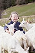 Kleines Mädchen mit Jungziegen auf einer Almwiese