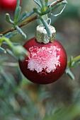 Weihnachtskugel mit Raureif am Tannenbaum