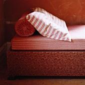 Oranges Bett mit Streifen- und Karomuster; den Bettkasten ziert ein florales Motiv