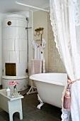 Badezimmer im traditionellen Stil mit antiker, freistehender Badewanne und einem runden Kachelofen