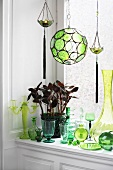 Potted plant, candlestick, vases and glasses by window
