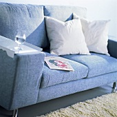 Blue couch with cushions, book and a glass of water