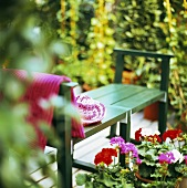 Garden bench with straw hat and geraniums