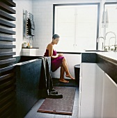 Woman wrapped in bath towel sitting in bathroom