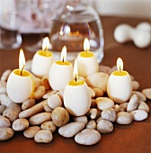 Egg-shaped candles on pebbles