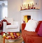 Wohnzimmer mit brennendem Feuer im Kamin, Kerzendeko auf dem Kaminsims und einem plüschigen roten Sofa mit weißem Fellkissen