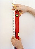 Hand holding a spirit level against the wall