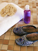 Woman's slippers, towel, sponge and small bottle