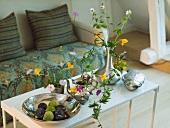 Couchtisch mit silberner Obstschale mit Keramikfeigen, einer silbernen Kanne und Wiesenblumen in einer silbernen Vase