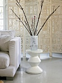 Twigs in vase on side table in front of screen