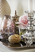 Silver candlestick, peony and carafe on tray