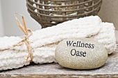 Stone with the words 'Wellness Oase' (Oasis of Wellness) and towels