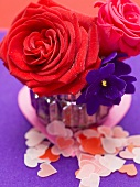 Red roses and African violets in vase, paper hearts