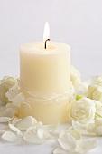 Brennende weisse Kerze mit Rosen